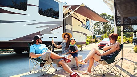 Mother,father,son and grandmother sitting near camping trailer,smiling.Woman,men,kid relaxing on chairs near car.Family spending time together on vacation near sea or ocean in modern rv park
